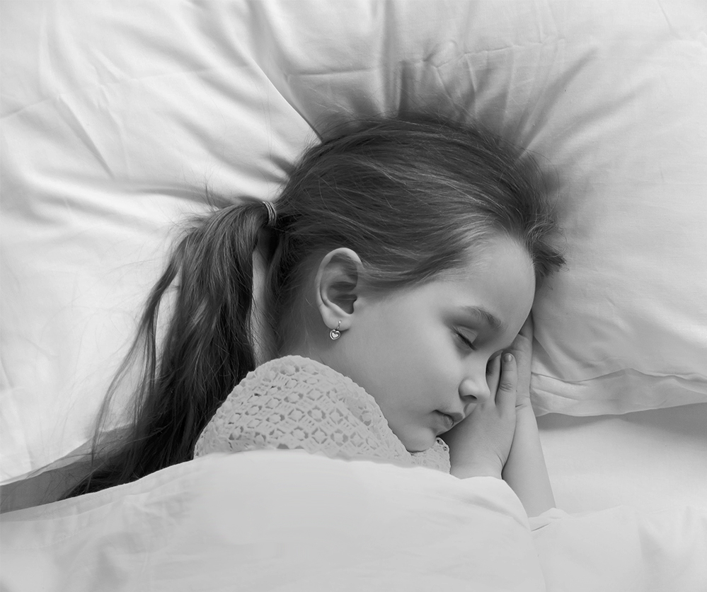 Calm adorable child lying on soft pillows taking day nap under warm blanket