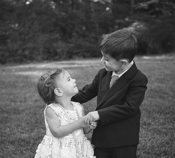 Warner and Lilli dressed for a ball and dancing in a field